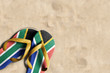 canvas print picture - Thongs with flag of South Africa, on beach sand