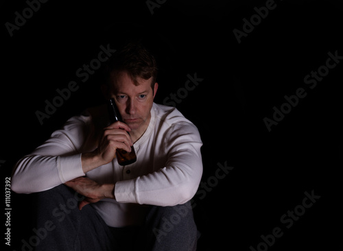 Valokuva  Mature man in thought while drinking beer in dark background