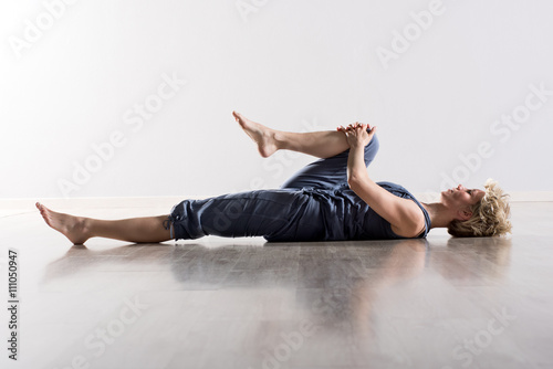 Woman holding knee while stretching hamstring Fototapeta