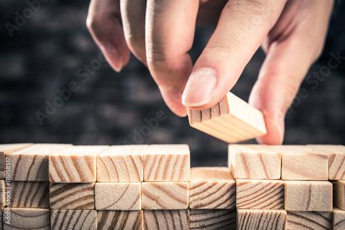 Photo 木製のブロックを積み上げている手