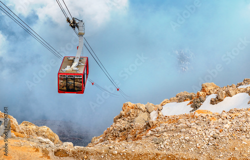 Spoed Foto op Canvas Gondolas Cabin of ropeway in mountains among clouds in the sky.