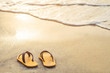 Yellow flip flop on the beach with bright light of sunset in summer