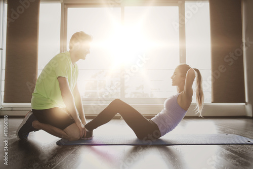 Keuken foto achterwand Ontspanning woman with personal trainer doing sit ups in gym