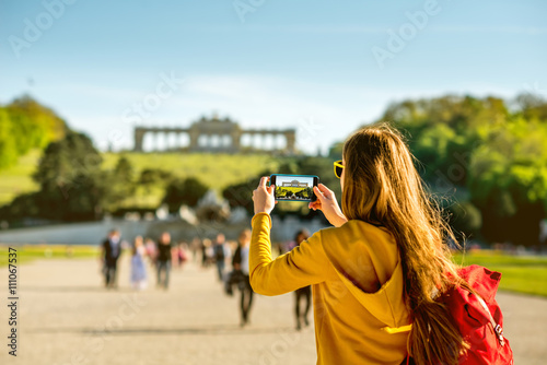 Garden Poster Vienna Young female tourist photographing with phone Gloriette building in Schoenbrunn palace in Vienna