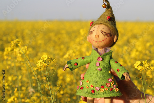 Textile handmade doll toy girl in green dress with green hair with a ladybug in the female hand