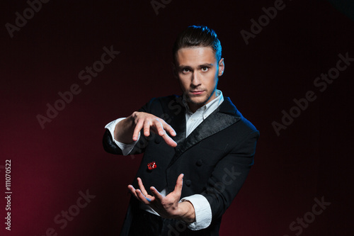 Canvas Print Confident young man magician showing tricks using one flying dice