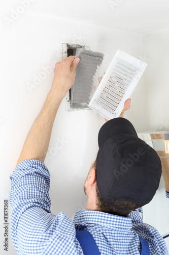 Fotografija  Handwerker öffnet Deckel mit Filter eines Luftschachtes zum Filterwechsel