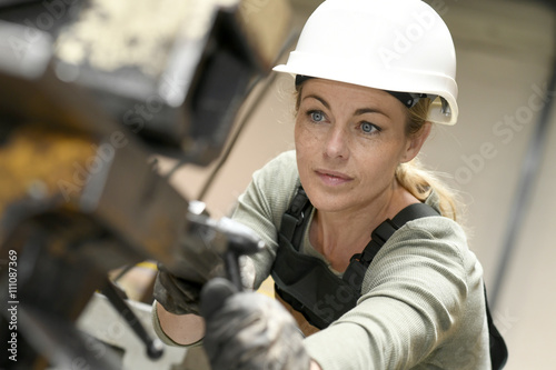 Fotografie, Obraz  Woman with helmet working in metallurgy factory