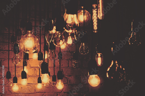 Incandescent lamps on a brick wall background. Wallpaper Mural