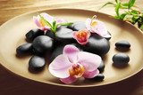Fototapeta Kuchnia - Spa stones and orchid flowers in plate on wooden table closeup