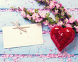 Fresh pink sakura flowers, decorative red heart and empty tag