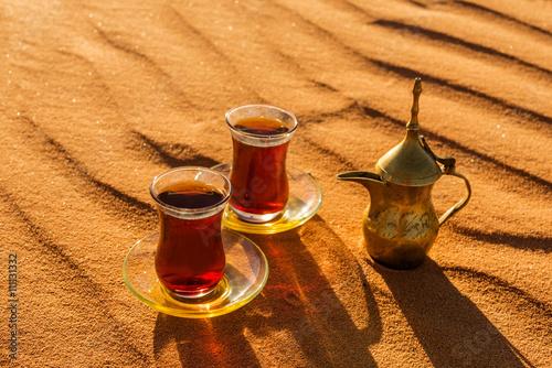 Fotografie, Obraz  Arabic tea in traditional glasses and pot on desert at sunset