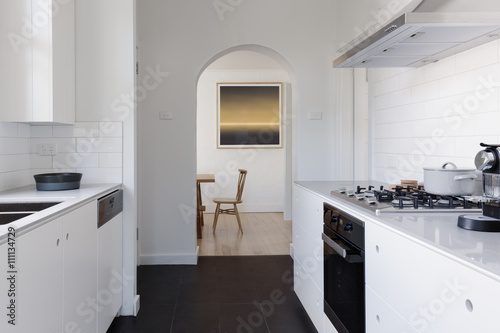 Fotografija  View of dining room at the end of a contemporary white galley ki