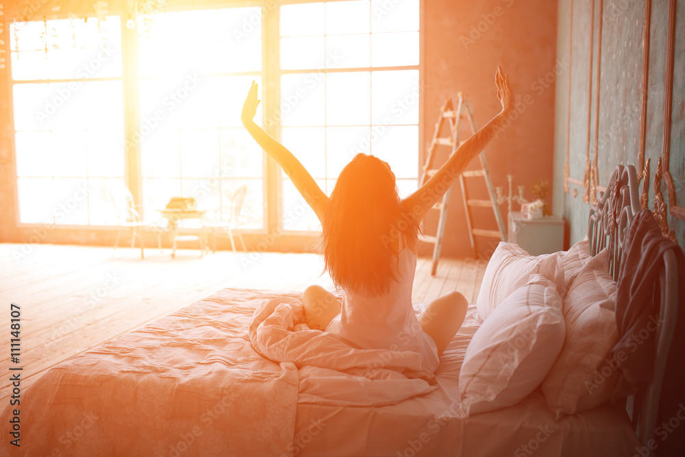Fototapety, obrazy: Woman stretching in bed after wake up