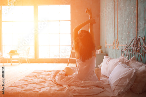 Obraz Woman stretching in bed after wake up - fototapety do salonu
