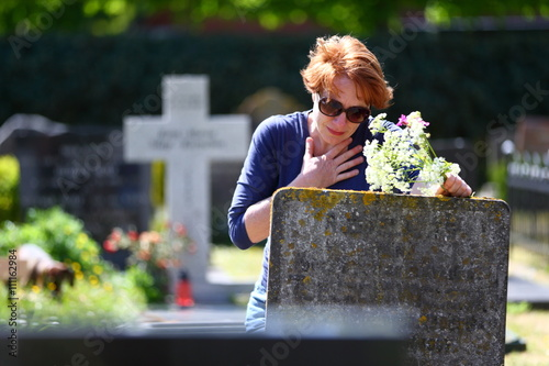 Photo mourning/ woman mourning a deceased loved one on a graveyard