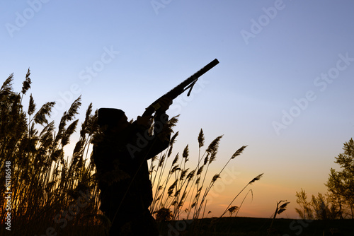 Foto op Canvas Jacht Hunter silhouette at sunset on the lake