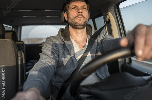 Tired unshaven man is driving the car
