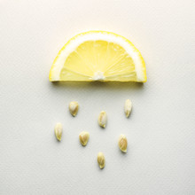 Sour Rain / Creative Concept Photo Of A Lemon Slice With Seeds Falling Down On Grey Background.