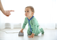 Mother Scolding Her Baby Who Is Playing With Plug