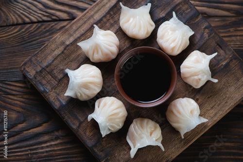 Dim sum dumplings on a rustic wooden serving board, top view Canvas Print