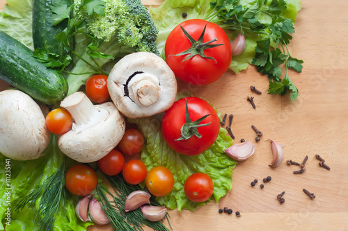 Fotografie, Obraz  Vegetables on wood background, mushrooms, cucumbers, tomatoes, broccoli, lettuce