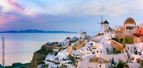 Poster Light pink Panoramic famous view, Old Town of Oia or Ia on the island Santorini, white houses and windmills at sunset, Greece
