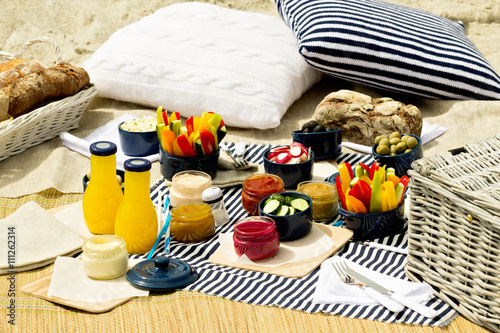 Staande foto Picknick Summer picnic on the beach. Serving picnic utensils blue with ve