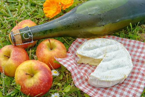 Photo apples with cider and camembert in the grass