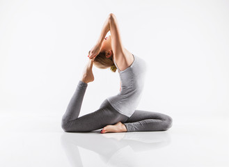 Naklejka Pretty sporty blonde in doing yoga on white background