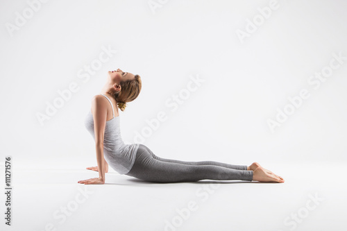 Pretty sporty blonde in doing yoga on white background