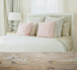 wooden table top with blur of luxury bedroom interior with pink pillows on bed