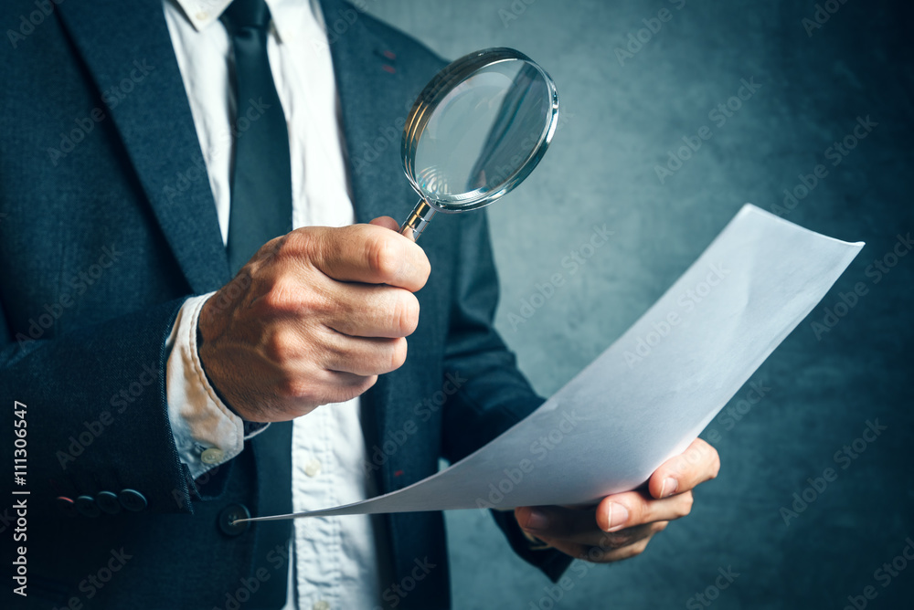 Fototapeta Tax inspector investigating financial documents through magnifying glass