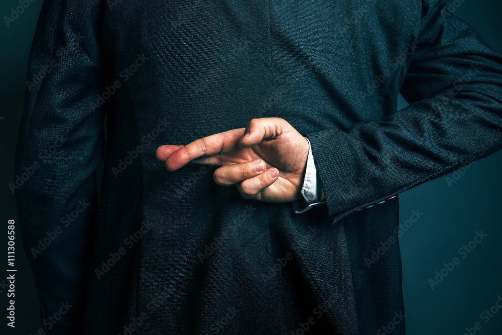 Fototapeta Lying businessman holding fingers crossed behind his back