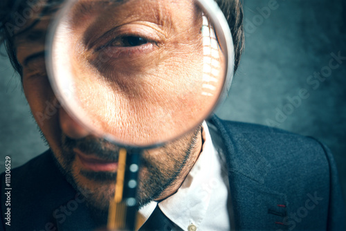 Fotografia Enlarged eye of tax inspector looking through magnifying glass