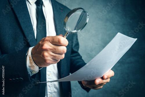 Fototapeta Tax inspector investigating financial documents through magnifyi obraz