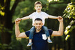 happy little boy stretching out hands while his father carrying him on shoulders