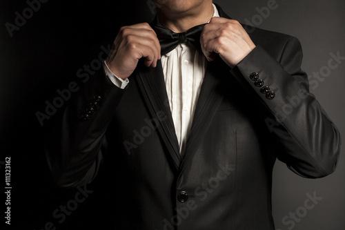 Fotografía Primer plano de caballero que lleva el lazo negro se arregla la corbata de moño
