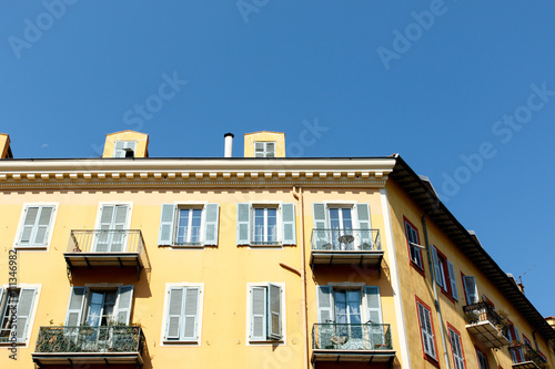 Yellow apartment building in Nice, France, with balconies and a blue sky background.