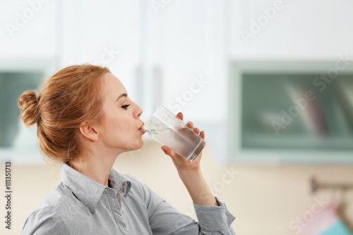 Fotografia, Obraz Young woman in the kitchen drinking water