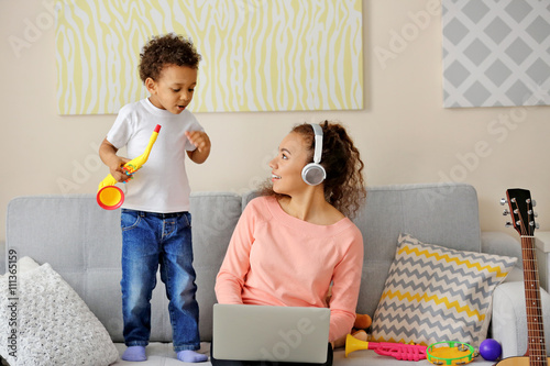 Fotobehang Indiërs Young woman in headphones and little boy playing with toy saxophone.