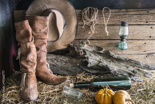 Deurstickers Retro Still life photography with traditional leather boots and american west rodeo brown cowboy hat in vintage ranch barn background
