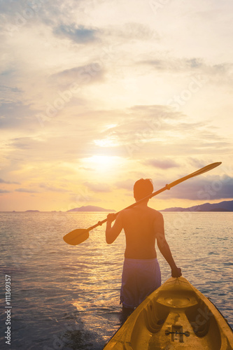 Photo  a guy pulling kayak to the sea in sunset, vacation holiday summertime concepts,