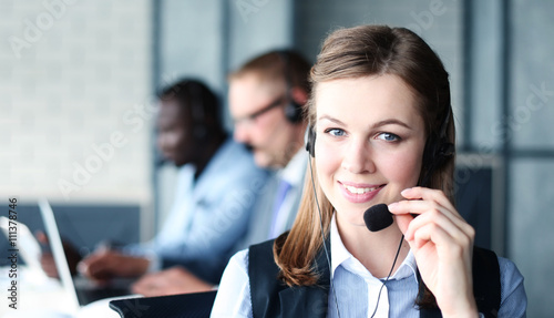 Fotografía  Portrait of call center worker accompanied by her team