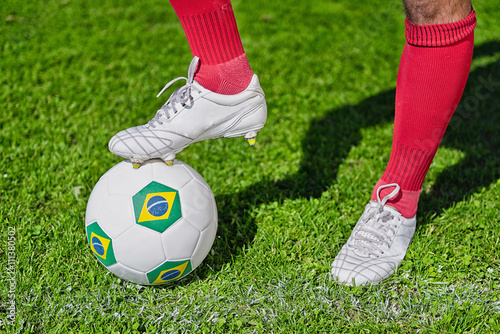 Fotografiet  Kick off Brazil. Soccer player, foot on ball with Brazilian flags