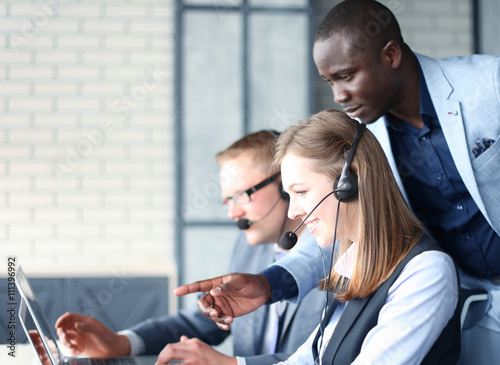 Fotografía  Phone operator working at call centre office helping hiss colleague