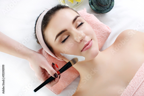 Woman with clay facial mask in beauty spa. Fotobehang