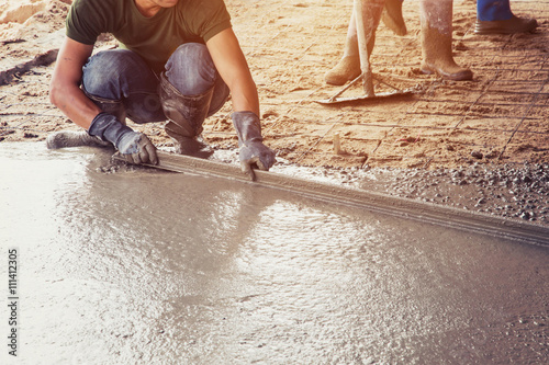 Plasterer screed concrete for floor in building Canvas Print