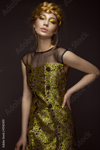 Tela  Beautiful girl in a gold dress with creative makeup and braids on her head