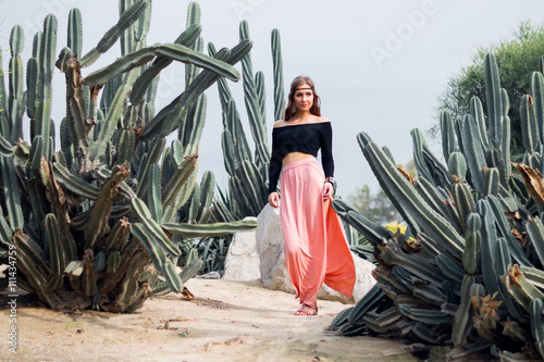 Photo  Hippie woman in long pink skirt walking near big cactuses